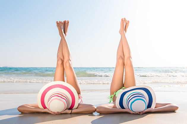 women in bikini enjoy on the beach by take legs up to sky